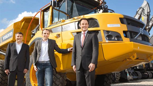 drei Männer im Anzug stehen vor einem großen, gelben Baufahrzeug