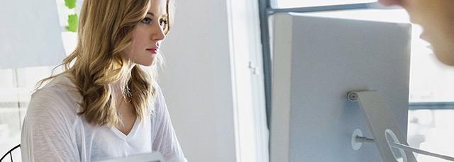 Frau im Office sieht in Bildschirm