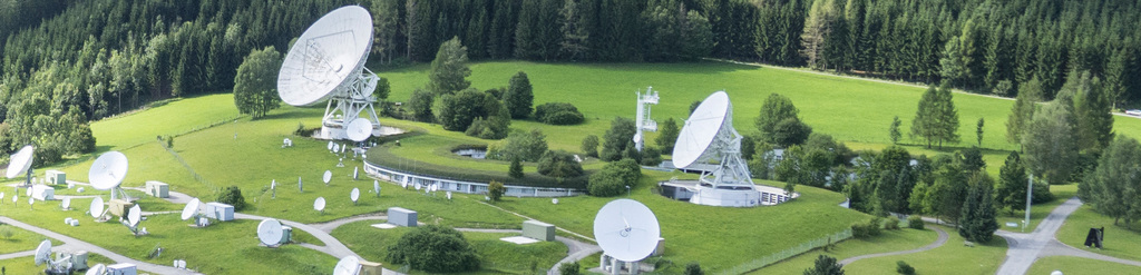 grüne Landschaft in der viele Satellitenschüssel in unterschiedlichen Größen aufgebaut wurden