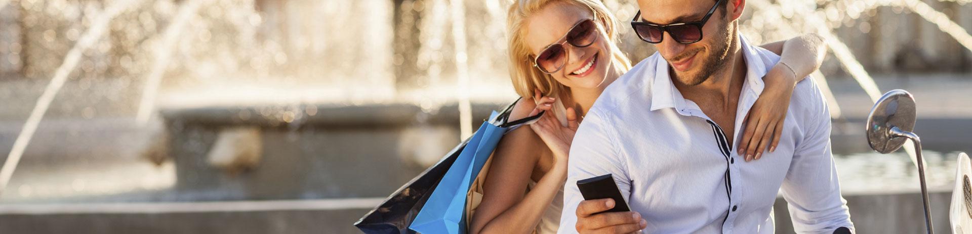 Glückliches Pärchen, das gemeinsam auf ein Smartphone schaut