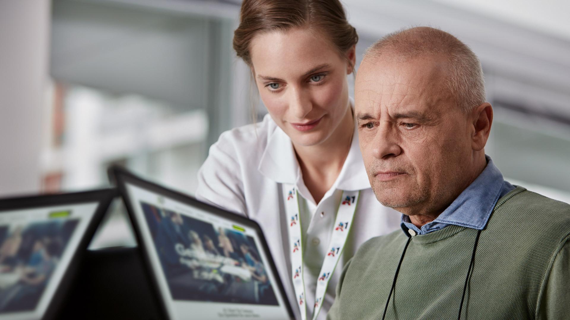 eine A1 Mitarbeiterin sieht einem älteren Herren über die Schulter; im Vordergrund sieht man verschwommen 2 kleine Bildschirme