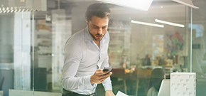 Geschäftsmann, der an seinem Arbeitsplatz steht und auf sein Smartphone schaut
