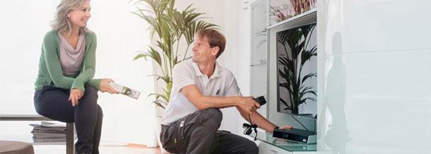 Guru Techniker hilft einer Frau bei TV Installation