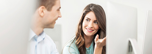 eine Frau und ein Mann sitzen vor einem Bildschirm und lächeln