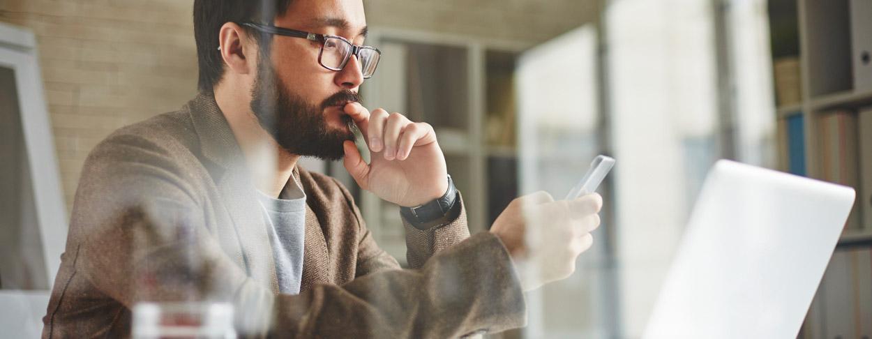 Mann sitzt mit seinem Smartphone vor dem Laptop