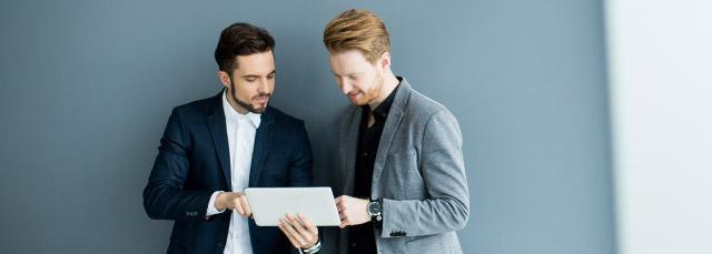 zwei junge Herren im Anzug stehen vor einer grauen Wand und sehen auf ein Tablet