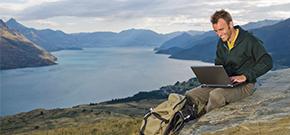 Mann sitzt mit seinem Laptop auf einem Hügel mit Weitblick über einen See und Berge.