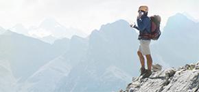 Ein Mann steht auf einem Berggipfel, ausgerüstet mit Helm, Rucksack und Wanderschuhen und telefoniert mit seinem Smartphone.