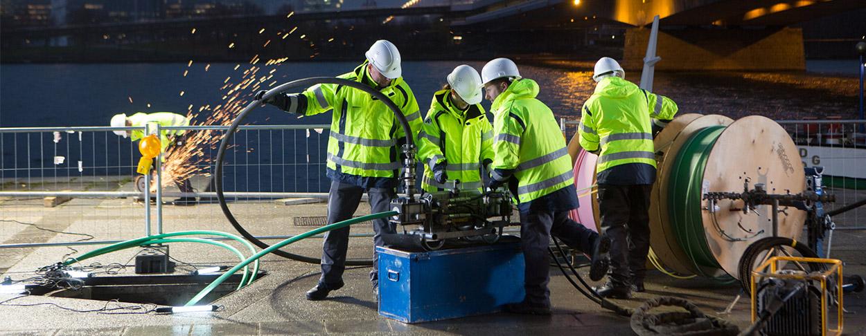 5 Männer mit Bauarbeiterhelme, die dabei sind Glasfaserkabel zu verlegen