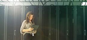 eine Frau steht mit ihrem Tablet vor einem großen Serverschrank