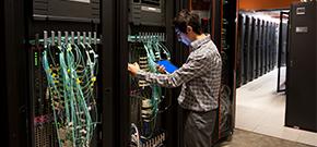 Mann steht mit einem Tablett in der Hand in einer Server-Farm und kontrolliert unterschiedliche Anschlüsse